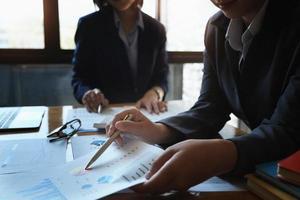 der Mitarbeiter des Unternehmens zeigt auf das Dokument, um das Budget zu berechnen und die Richtigkeit der Investition zu überprüfen. foto
