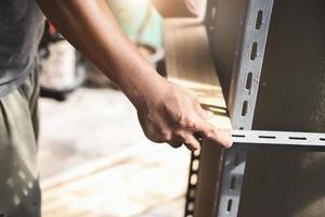 ein Handwerker legt ein Holzbrett auf ein Stahlregal, das er in seiner Freizeit zusammengebaut hat foto
