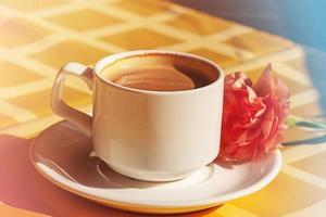 Tasse Kaffee. Tasse Kaffee mit Milch in einer weißen Tasse am Morgen. Nelkenblume auf einer Untertasse. foto