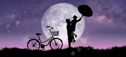 Silhouette in der Nachtlandschaft von Paaren oder Liebhabern, die bei Vollmond tanzen und singen foto