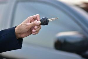 Verkäufer, der den Schlüssel des Autos und des geparkten Autos hält foto