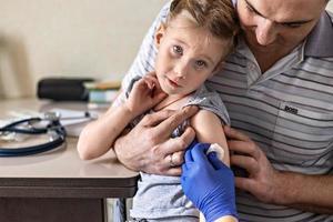 Ein kleines Mädchen mit ihrem Vater in der Arztpraxis der Klinik wird gegen das Coronavirus geimpft. das konzept der impfung, immunisierung, prävention gegen covid-19. foto