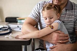 Impfung eines kleinen Mädchens in den Armen ihres Vaters in der Arztpraxis gegen das Coronavirus. lustiges klebepflaster für kinder. Impfung gegen Covid-19, Grippe, Infektionskrankheiten. foto