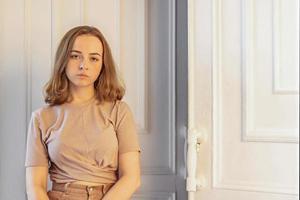 Ein süßes, stilvolles junges Mädchen sitzt in der Tür ihres Zimmers. Teenager. Traurigkeit foto