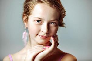 Nahaufnahmeporträt eines jungen Mädchens mit festlichem Make-up für eine Party. Valentinstag. Ohrringe-Federn in den Ohren des Models foto
