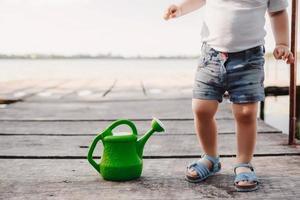 ein kleines Mädchen spielt mit einer Gießkanne einer Holzbrücke. Frühling und Sommer. Gartenarbeit. grüne Gießkanne foto