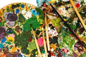 Palette mit bunten Farben. bunte Ölgemälde-Palette mit einem Pinsel, der hineinreicht. Pinsel und Farben zum Zeichnen. foto