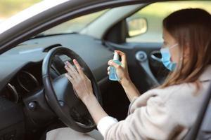 Sprühen von antibakteriellem Desinfektionsspray im Auto, Infektionskontrollkonzept. Desinfektionsmittel zur Vorbeugung von Coronavirus, Covid-19, Grippe. Sprühflasche. Frau, die eine medizinische Schutzmaske trägt, die ein Auto fährt. foto