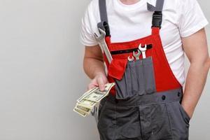 Zugeschnittenes Foto von Arbeiter in roter Uniform, Schutzhelm mit Bündel von Dollar, Bargeld auf weißem Hintergrund. männlicher Arbeiter für Werbung. Weltwirtschaftskrise und Arbeitsplatzverlustkonzept.