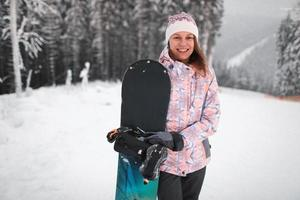 glücklich lächelnde junge Frau mit Snowboarden auf dem Berg im Winter foto