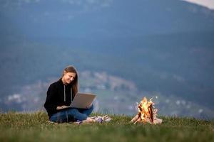 junge frau freiberuflerin mit laptop in den bergen am abend. Touristenmädchen, das am Lagerfeuer sitzt foto