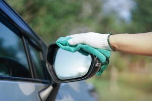 Reinigung des Autos mit grünem Mikrofasertuch im Freien im Urlaub. foto