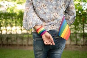 asiatische dame, die regenbogenfarbenfahne hält, symbol des lgbt-stolzmonats, feiert jährlich im juni sozial für schwule, lesbische, bisexuelle, transgender, menschenrechte foto