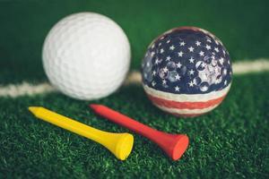 Golfball mit USA-Flagge und Tee auf grünem Rasen oder Gras, beliebtester Sport der Welt. foto