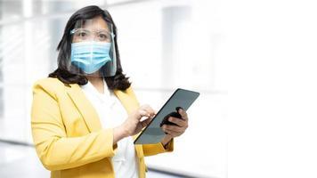 asiatische dame, die tablette hält und im büro eine neue normalmaske trägt, um die sicherheitsinfektion covid-19 coronavirus mit kopierraum zu schützen. foto