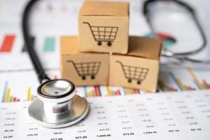 Stethoskop und Warenkorb-Logo auf der Box mit Taschenrechner auf Diagrammhintergrund. Bankkonto, investitionsanalytische Forschungsdatenwirtschaft, Handel, Online-Unternehmenskonzept für den Geschäftsimport und -export. foto