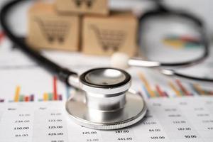 Stethoskop auf Diagrammen und Diagrammpapier mit Logo-Box für Einkaufskarten, Finanzen, Konto, Statistik, Investitionen, analytische Exportdatenwirtschaft und Geschäftskonzept. foto