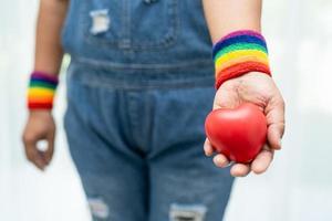 asiatische dame, die regenbogenflaggenarmbänder trägt und rotes herz hält, symbol des lgbt-stolzmonats, feiert jährlich im juni sozial für schwule, lesbische, bisexuelle, transgender, menschenrechte. foto