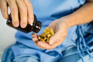 Asiatischer Arzt hält und gießt und hält Vitamin-C-Pillen aus der Flasche an den Patienten zur Behandlung von Infektionen im Krankenhaus, Konzept der Apotheke. foto