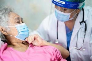 asiatischer arzt, der einen neuen normal trägt, um den patienten mit maske zu überprüfen, schützt die sicherheitsinfektion covid-19-Coronavirus-Ausbruch in der quarantänekrankenhausstation. foto
