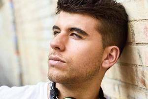 hübscher junger Mann mit blauen Augen, die nahe einer Wand aufwerfen foto