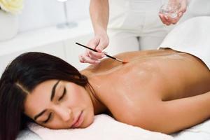 Frau, die eine Rückenmassage mit Ölbürste im Spa-Wellnesscenter erhält foto