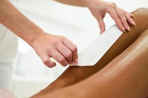 Frau mit Haarentfernungsverfahren am Bein mit Wachsstreifen foto