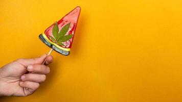 schöner süßer roter Lutscher mit Marihuana in der Hand auf gelbem Hintergrund, Süßigkeiten mit Cannabis foto
