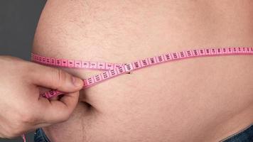 Fettleibigkeitskonzept, messen Sie einen großen fetten Bauch mit einem Zentimeter cent foto
