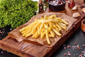 frische scharfe Pommes frites mit Salzgemüse und Gewürzen foto
