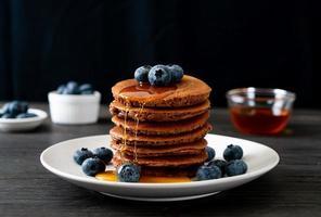 Schokoladenpfannkuchenstapel mit Heidelbeeren und Honig auf einem Teller foto