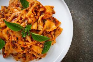 Farfalle Nudeln mit Basilikum und Knoblauch in Tomatensauce - italienische Sauce foto