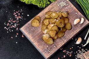 leckere salzig-würzige eingelegte Gurke mit Ringen auf einem Holzbrett geschnitten foto