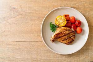 gegrilltes und gegrilltes Schweinefiletsteak mit Mais, Karotte und Tomaten foto