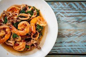 gebratene Meeresfrüchte von Garnelen und Tintenfisch mit thailändischem Basilikum - asiatische Küche foto