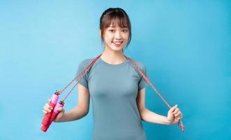 junge asiatische frau, die sportanzug auf blauem hintergrund trägt foto