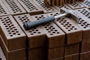 ein Hammer wird auf einen roten Backsteinstapel gelegt. foto