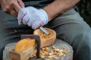 Handwerker zeigt den Prozess der Herstellung von Holzlöffeln foto