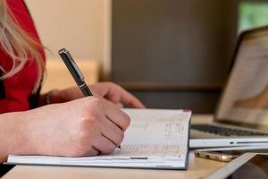 blonde Frau sitzt an einem Laptop und schreibt. Auf dem Tisch liegen ein Laptop, ein Tablet, ein Telefon und ein Notebook. foto