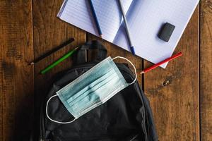 Schutzmaske und Schultasche, Schulmaterial auf der Schulbank, Coronavirus-Maßnahmen und zurück zum Schulkonzept foto