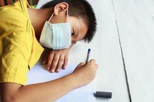 Bildungs-, Schul- und Pandemiekonzept - Schülerjunge mit medizinischer Gesichtsschutzmaske zum Schutz vor Viruserkrankungen foto