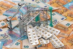 Einkaufswagen mit Tabletten auf Euro-Scheinen foto
