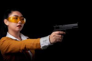 asea frau trägt einen gelben anzug mit einer hand hält eine pistole auf schwarzem hintergrund foto