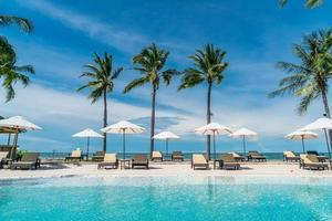 Stuhlpools oder Liegen und Sonnenschirme rund um den Pool mit Meereshintergrund - Ferien- und Urlaubskonzept foto