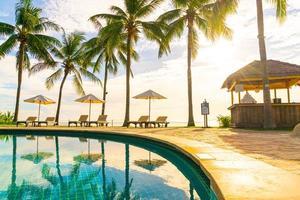 Wunderschöne Luxus-Sonnenschirme und -Stühle um einen Außenpool im Hotel und Resort mit Kokospalmen bei Sonnenuntergang oder Sonnenaufgang - Urlaubs- und Urlaubskonzept foto