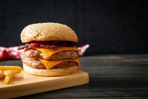 Schweinefleisch-Hamburger oder Schweinefleisch-Burger mit Käse, Speck und Pommes frites foto