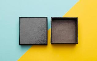 Black-Box-Verpackung auf halbblauem und gelbem Hintergrund foto