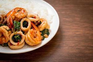 Reis und gebratene Meeresfrüchte von Garnelen und Tintenfisch mit thailändischem Basilikum - asiatische Küche foto