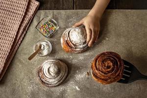 Kinderhand nimmt ein frisch gebackenes Zimtbrötchen foto