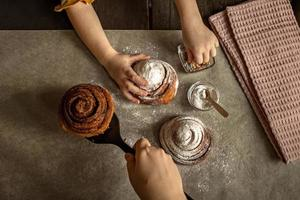 Kinderhände im Rahmen bestreut ein frisch gebackenes Brötchen mit Zimt mit Gebäckstreuseln foto